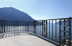 Balcony with custom iron railing overlooking beautiful lake and mountains