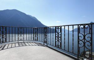 Balcony with custom iron railing overlooking beautiful lake and mountains