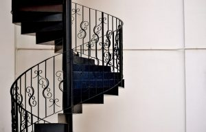 Winding staircase with ornate custom iron railing