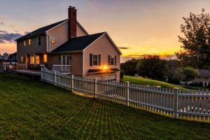 House with white fence facing a sunset