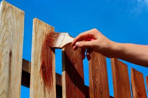 Closeup of person staining a wooden fence