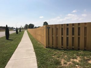 Wooden privacy fence along a sidewalk