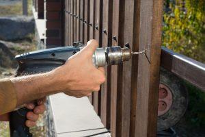 Man installing a dark wood fence