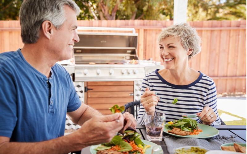 Senior couple having BBQ in their backyard