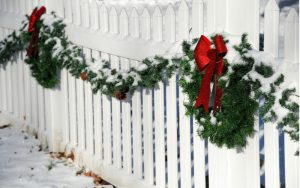 White fence decorate with Christmas wreaths
