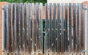 Dumpster enclosure protected by fencing.
