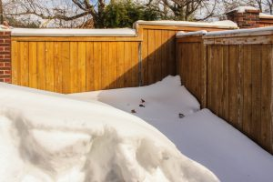 Deep snow piled up against wooden privacy fence